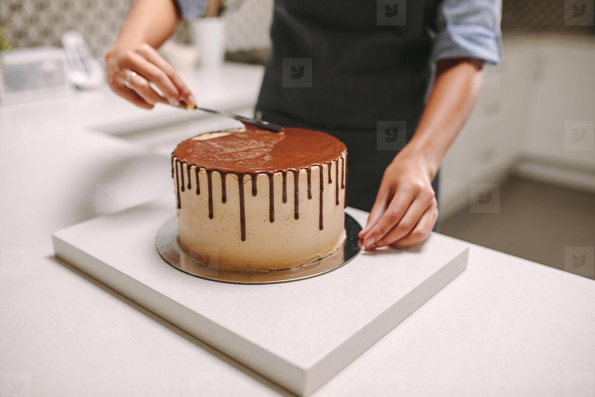 Confectioner decorates a cake with liquid chocolate