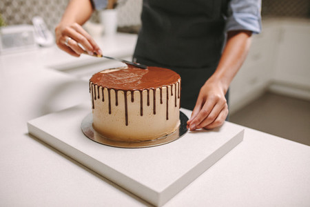 Confectioner decorates a cake with liquid chocolate