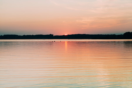 Sun hiding behind the horizon in the lake of chiemsee