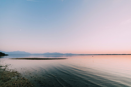 Amazing sunset in chiemsee lake with mountains in background