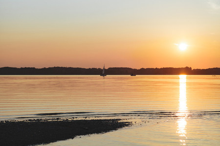 Amazing sunset in chiemsee lake with a sailboat navigating