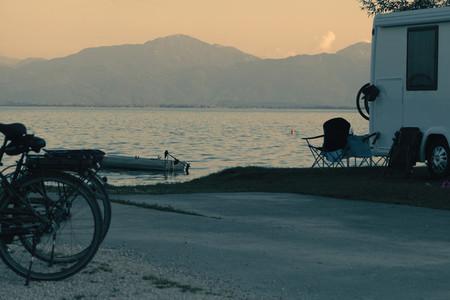 Man swimming on the lake near his caravan  observes the sunset