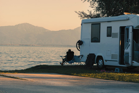 Man sitting near his caravan observes the sunset close the lake