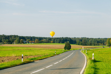 Yellow hot air balloon taking off near a county road in Germany