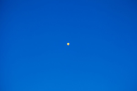 Yellow hot air balloon flying very high in the blue sky