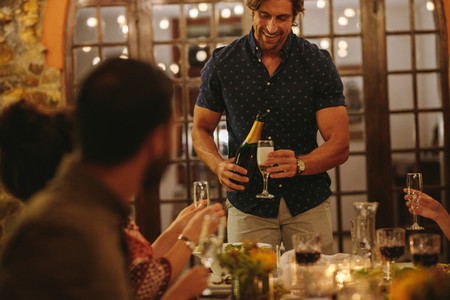 Man serving drinks to friends at party