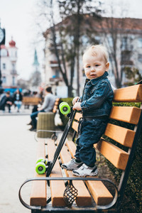 Young boy standing on the wooden bench in the park