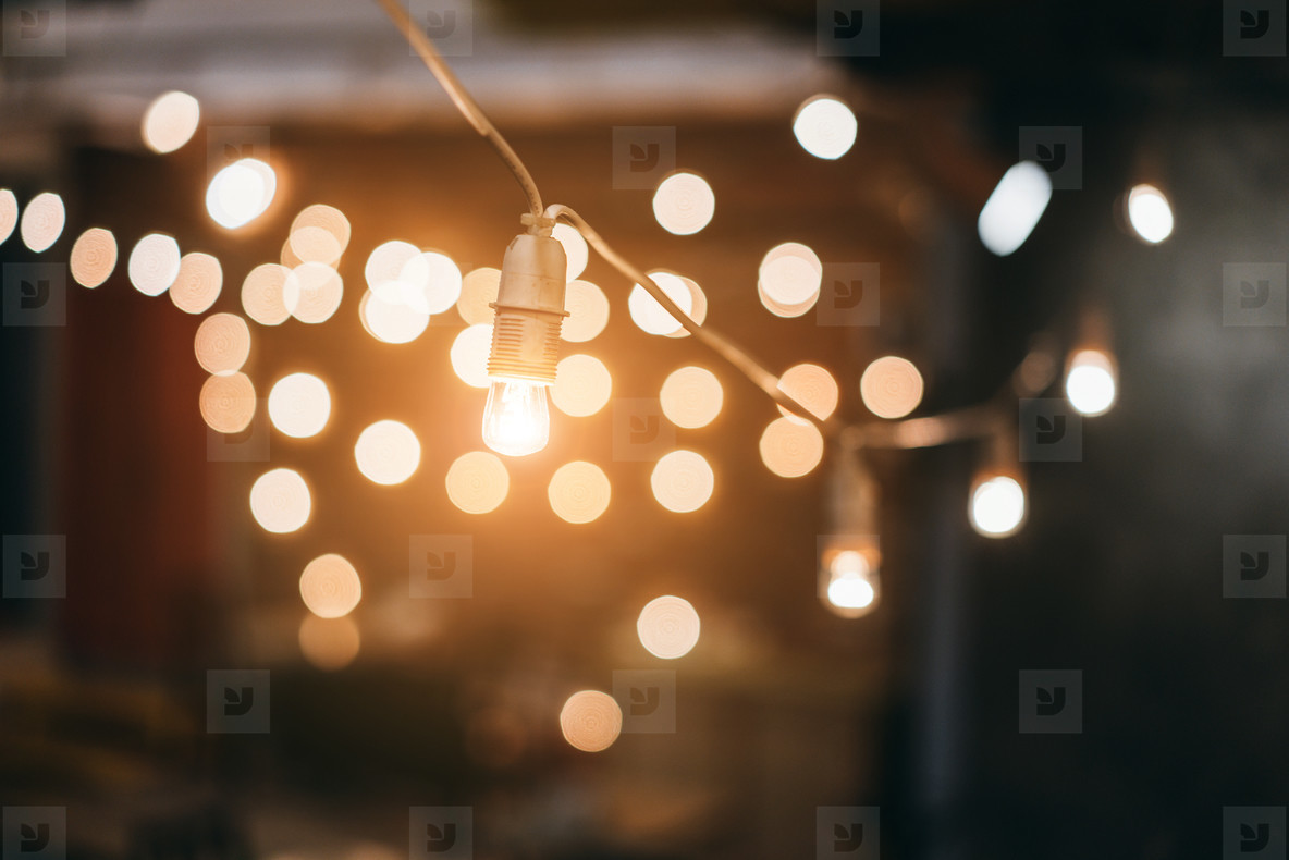Lamp on garland with lights on background