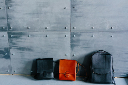 three leather bags on a gray background