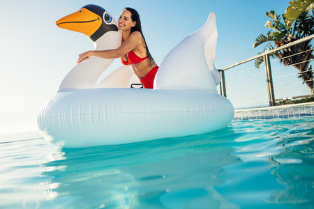 Beautiful woman on inflatable swan