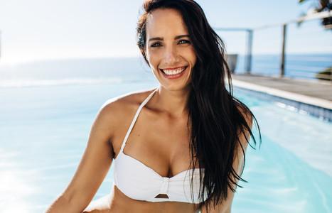 Attractive woman in bikini by the pool