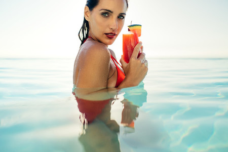 Woman in pool with cocktail