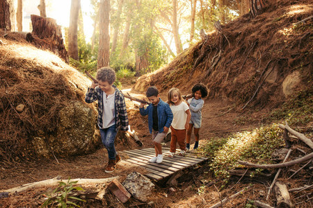 Group of children building camp in forest
