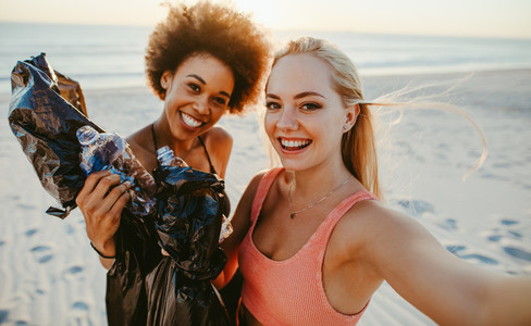 Women taking selfie after beach cleaning