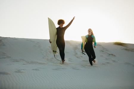 Surfers running down the beach