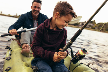 Father and son enjoying fishing in the lake