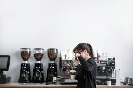 Female barista makes coffee