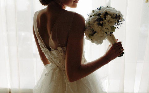 beautiful bride in a wedding dress  by window