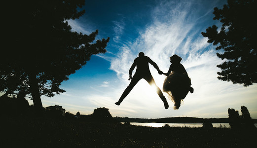 groom and bride jumping against the beautiful sky