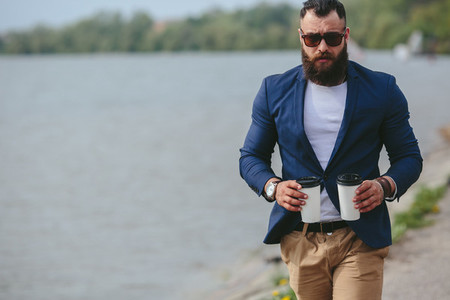 well dressed man carries coffee