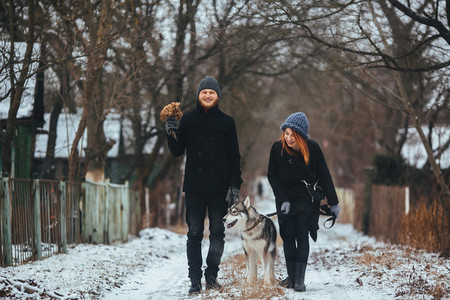 man and woman with dog walking