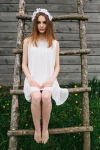 Lovely girl near a wooden house