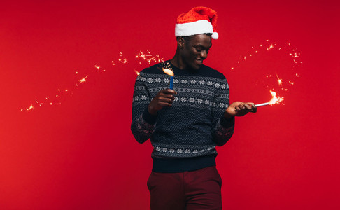 African man enjoying christmas with fireworks