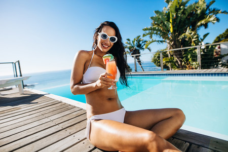 Woman relaxing by the pool with a fruit juice