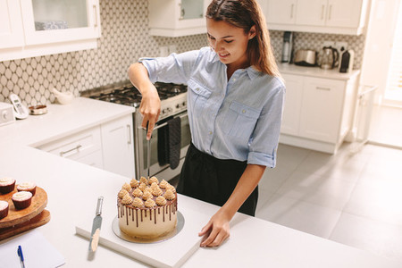 Pastry chef cutting a cake