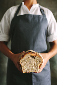 Woman baker with a bread loaf in bakery