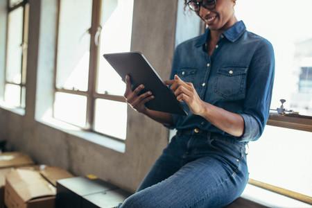 Female entrepreneur in office using digital tablet