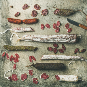 Spanish or Italian cured sausages in slices over concrete background