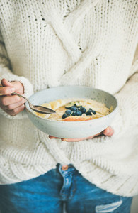 Woman in jeans and sweater eating oatmeal porriage with berries