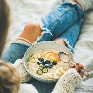 Woman in jeans and sweater eating vegan breakfast square crop