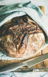 Freshly baked sourdough bread on chopping board selective focus