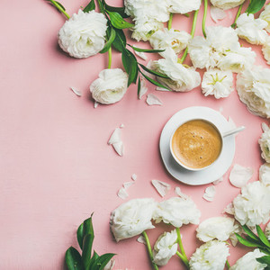 Flat lay of cup of coffee and ranunculus flowers  square crop