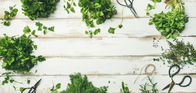 Various fresh green kitchen herbs over wooden background wide composition