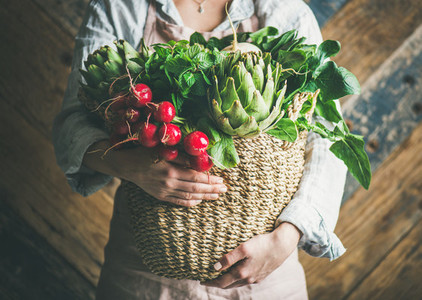 Female farmer holding basket of fresh garden vegetables horizontal composition