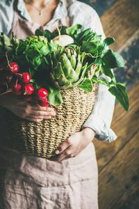 Female farmer in apron holding basket with fresh vegetables