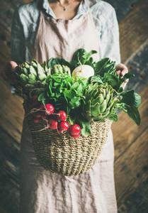 Female farmer holding basket of fresh garden vegetables and greens