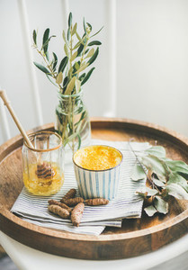Turmeric latte  golden milk with honey on wooden tray