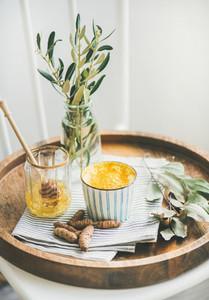 Turmeric latte golden milk with honey on wooden tray