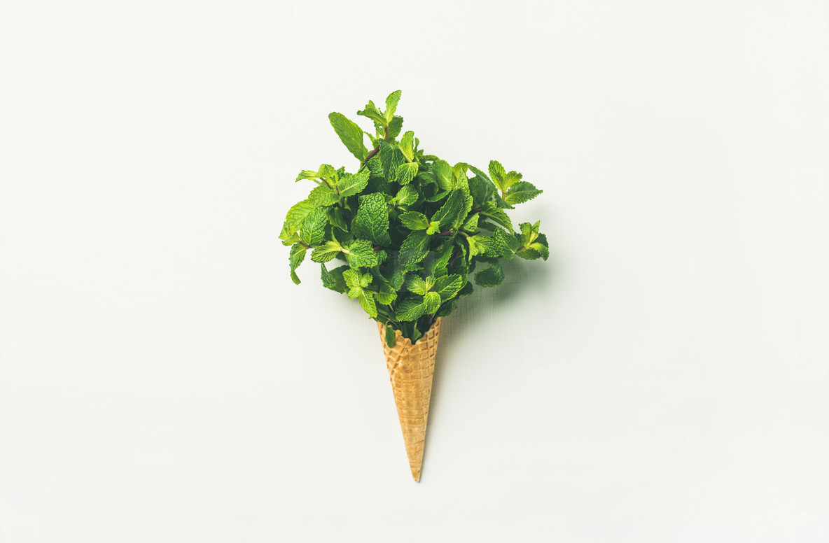 Waffle cone with fresh mint leaves over white background  flat lay