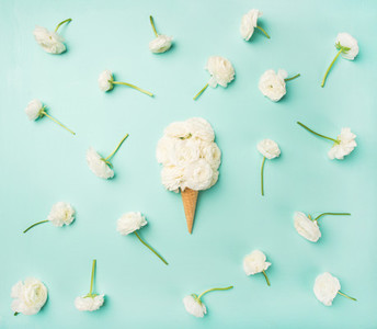 Waffle cone with white buttercup flowers over blue background
