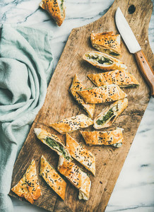 Freshly baked Turkish borek roll cut in slices on board