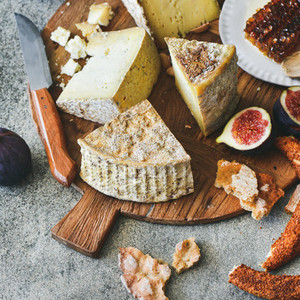 Cheese assortment figs honey fresh bread and nuts square crop