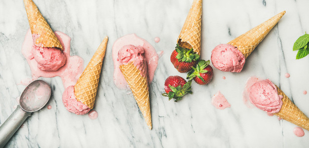 Flat lay of homemade yogurt strawberry ice cream over marble background