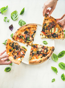 Peoples hands taking Freshly baked vegetarian pizza over marble background