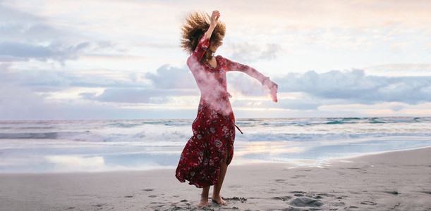 Woman dancing with smoke grenade at the beach