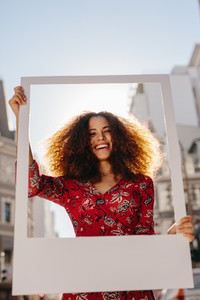 Beautiful woman holding a blank photo frame